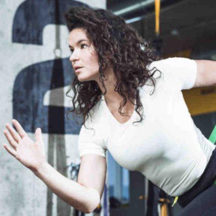 Fitness Frau, die vom Gummi zurückgehalten wird